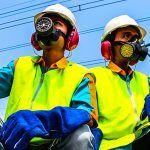 workers in hard hats, vests and respirators