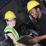 man and woman at work site going over safety checklist