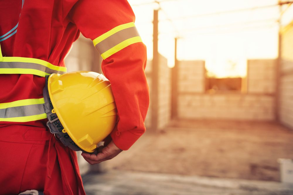 worker in ppe holds helmet at job site