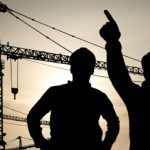 workers in hard hats at construction site pointing to crane