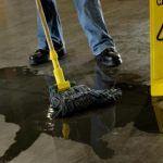 cleaning work floor with caution wet floor sign