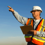 worker in hard hat with clipboard pointing