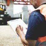 worker in vest going over safety checklist