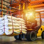 Worker uses forklift to safely transport material across ontario warehouse