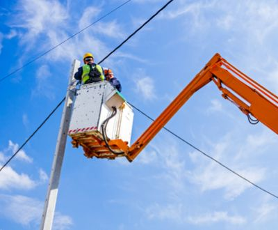 Workers in bucket lift work on wires safely