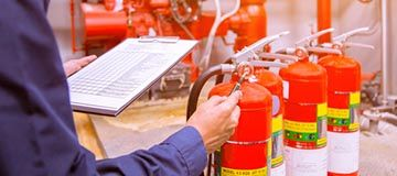 manager performing due diligence by inspecting fire extinguishers