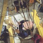 worker in hard hat on harness being lowered into well