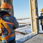 construction workers in safety gear harnesses