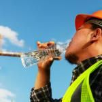 worker drinks water stays hydrated while outside in summer heat