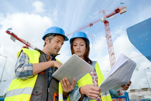 construction site with workers discussing plans