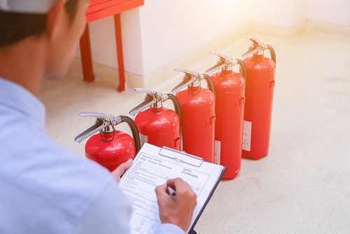 staff checking fire extinguishers