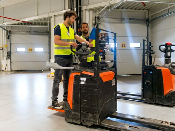 A worker leans how to operate a forklift
