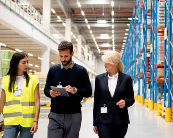 A manager, supervisor, and member of joint health and safety committee walk through a warehouse