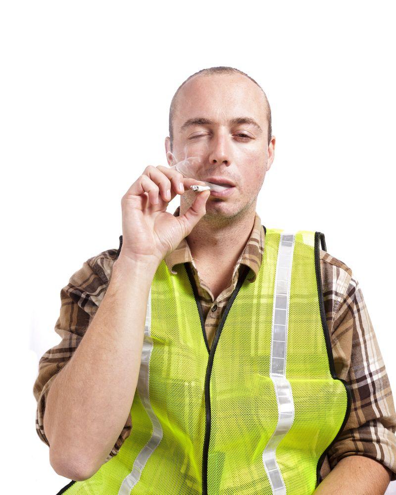 worker in safety vest smoking marijuana on the job