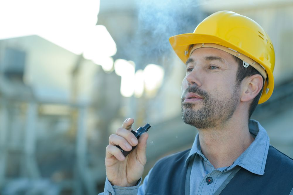 man vaping at construction site