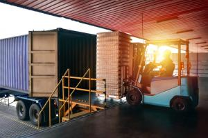 forklift at loading dock with trucks