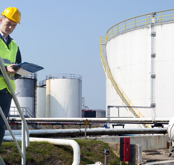 a worker takes notes on a clipboard with large oil terminals in the background