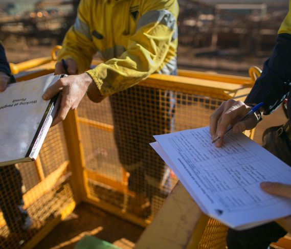 A construction worker hands a binder to a coworker