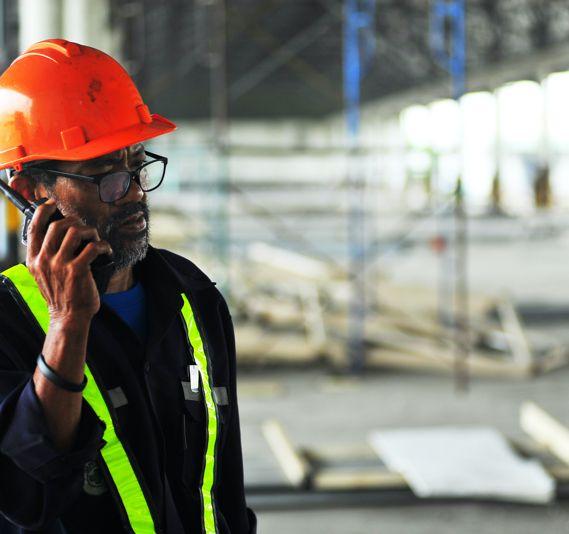 A construction worker speaks on a walkie talkie