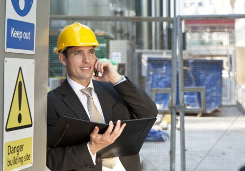 A supervisor talks on his cellphone while reviewing plans