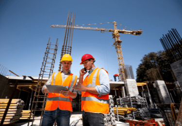 Two workers review plans at a construction site