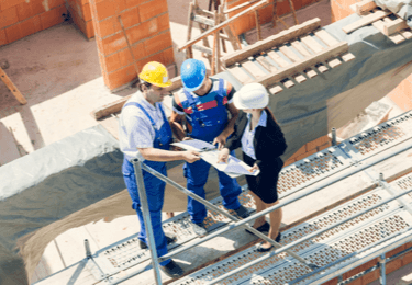Workers and a manager go over plans while standing on scaffolding