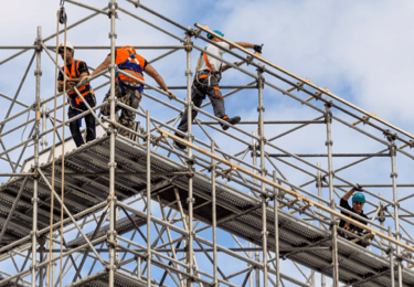 Construction workers safely work on scaffolding