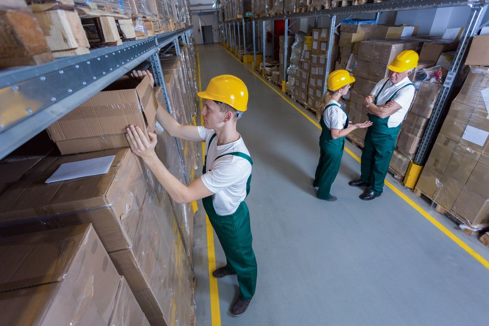 worker pulls boxes down from shelf materials handling