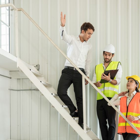 A manager speaks to members of the health and safety committee in a warehouse