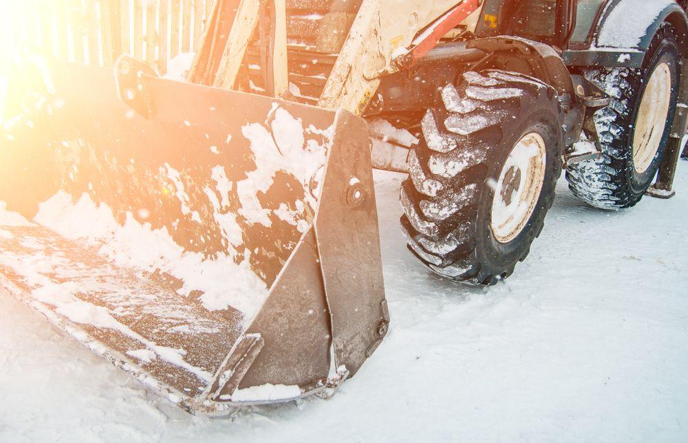 worker operating snowplow in winter