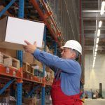A man safely lifting a box onto a shelf in a warehouse
