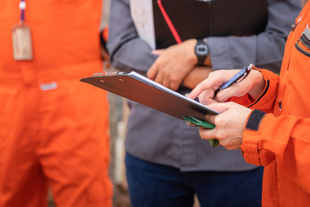 professional safety consultant talking to a group of working with a clipboard in hand