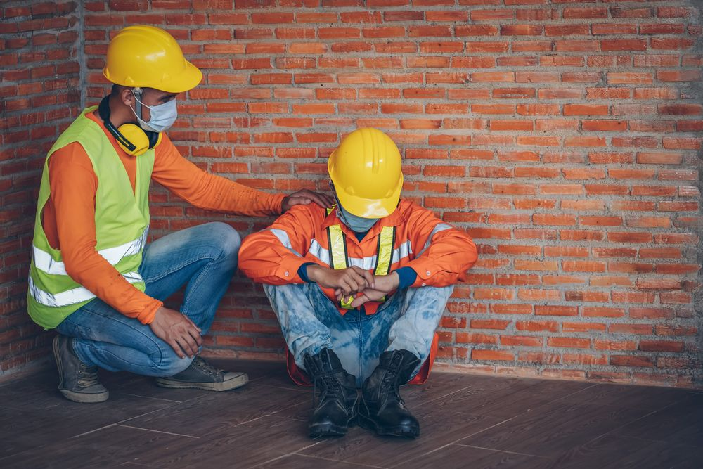 2 workers sitting by a brick wall with one of them comforting the other who is exhausted