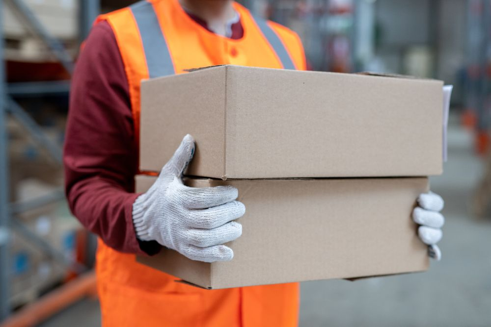 warehouse worker carrying cardboard boxes wearing white gloves to avoid injury