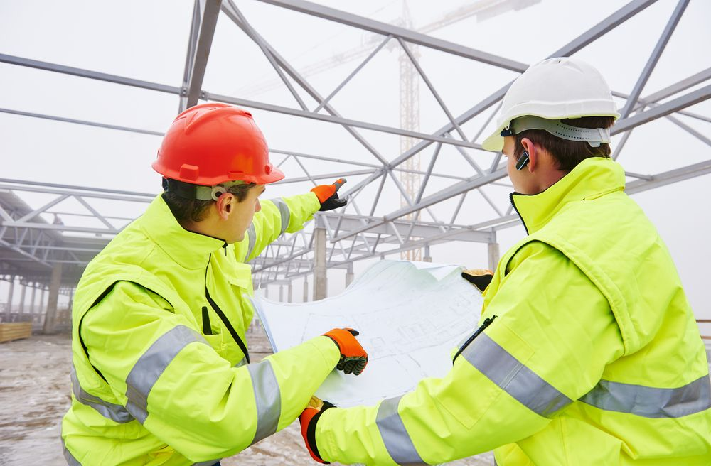 a safety leader wearing the proper equipment explaining best practices to a fellow employee