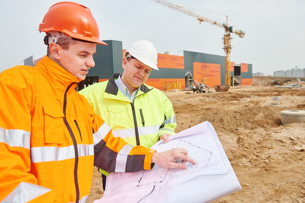 an employee wearing an orange safety coat talking to a safety leader about their project