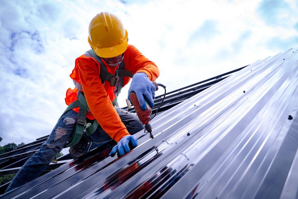 an employee working at heights installing metal sheeting