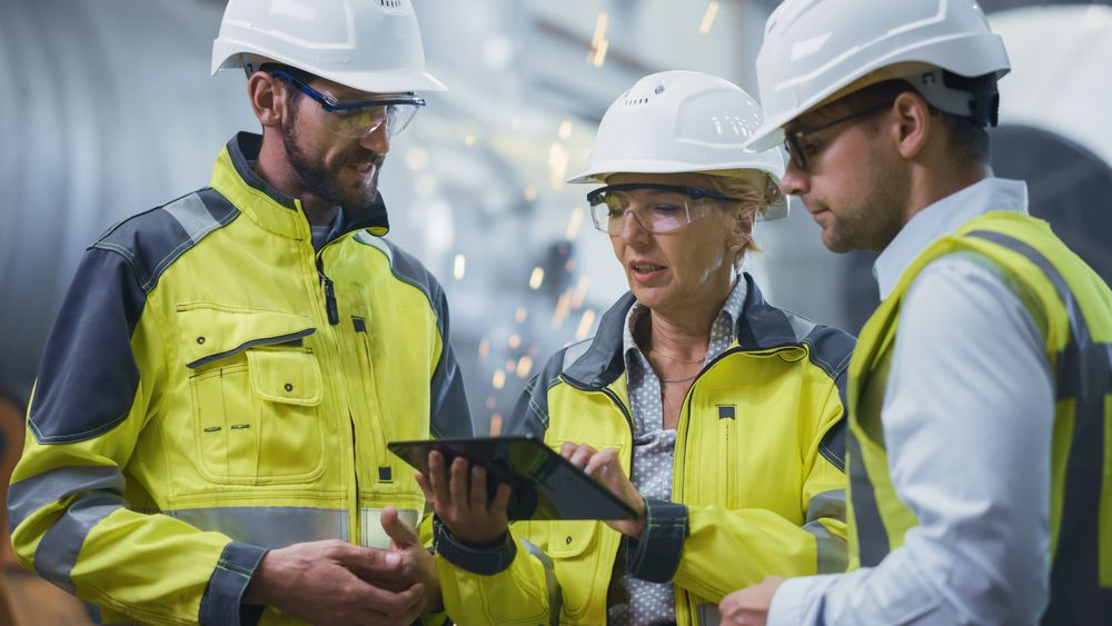 3 construction engineers working together on a device reviewing the safety program