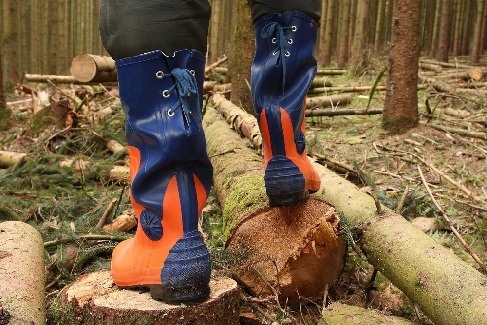 an arborist wearing the proper safety shoes to protect them while standing on a pile of chopped wood.