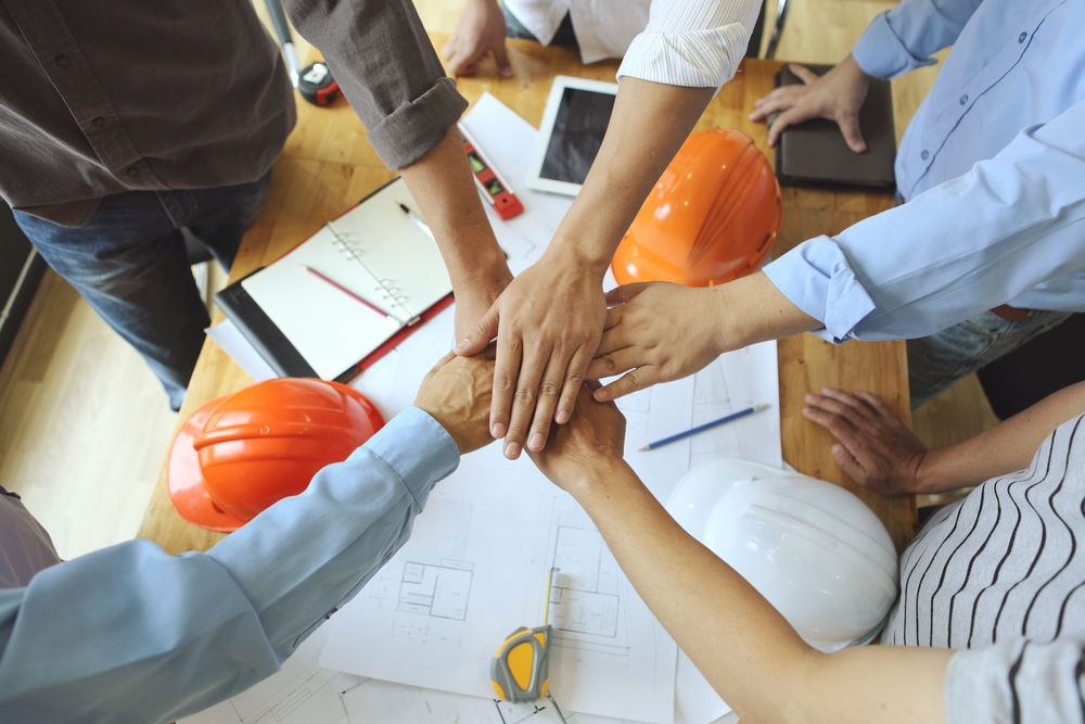 workers with their hands in a pile representing teamwork