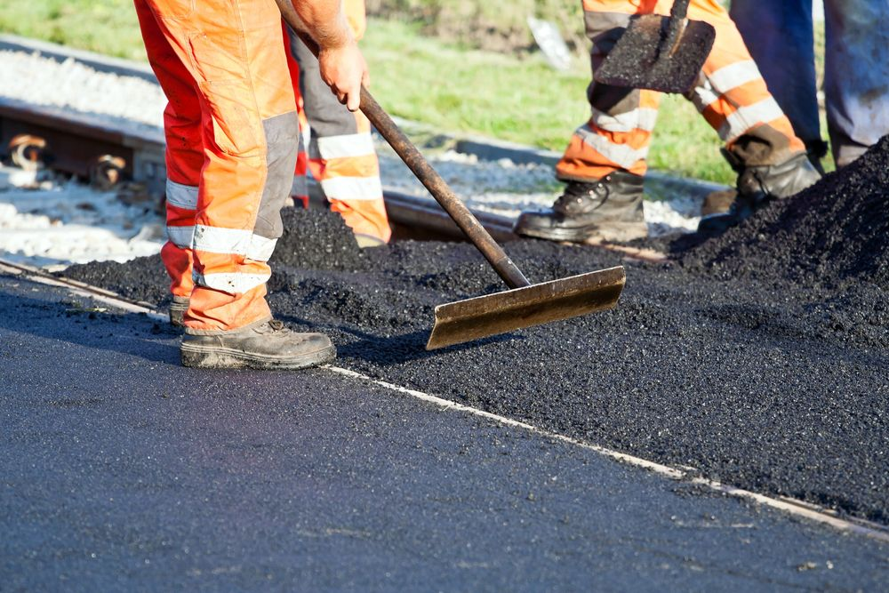a construction worker using equipment to flatten asphalt on the road