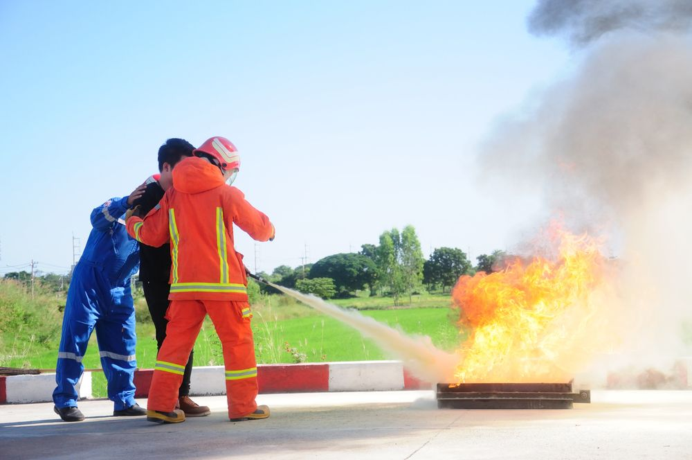 employee being trained on how to use a fire extinguisher